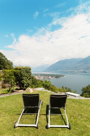 modern garden: garden of a villa, modern furniture, two sun lounger