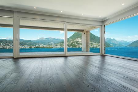 Interieur, modern huis, lege woonkamer met ramen met uitzicht op het meer