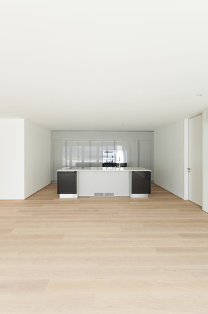 front room: empty apartment with hardwood floor, modern kitchen Stock Photo