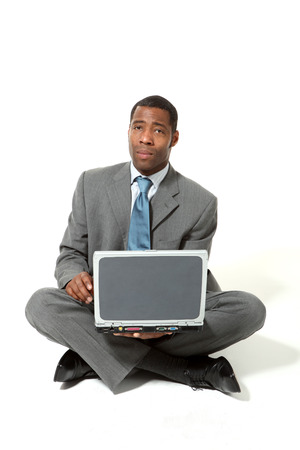 sitted: portrait of black businessman with laptop over white background