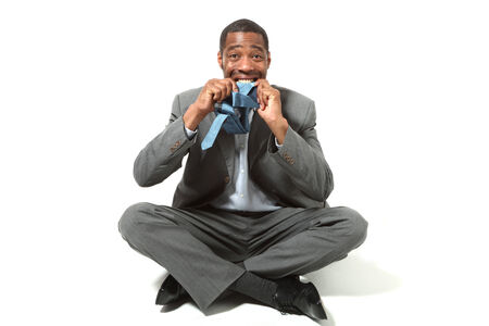 sitting down: portrait of black businessman, legs crossed, over white background Stock Photo
