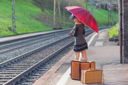 Woman waiting at the railway station with umbrella photo