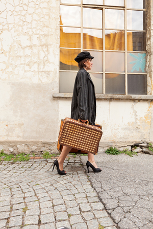 arrives: Woman with luggage arrives at destination Stock Photo