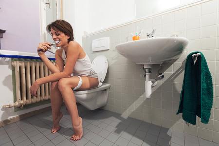 beautiful girl sitting on a toilet Stock Photo