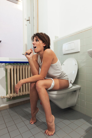 the piss: beautiful girl sitting on a toilet Stock Photo