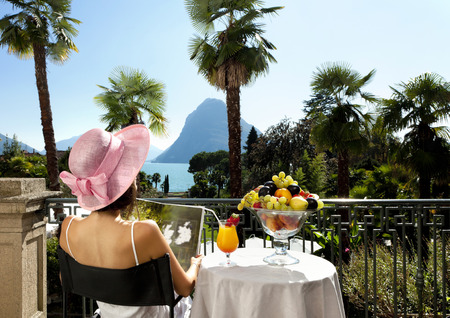 small table: portrait of beautiful woman on the terrace of prestigious hotel