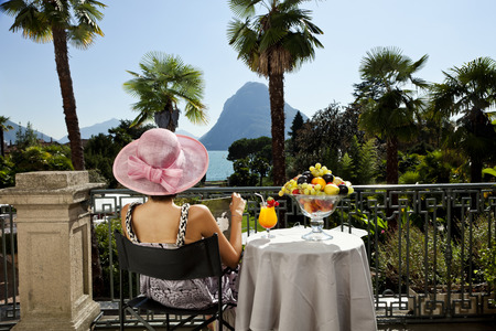 portrait of beautiful woman on the terrace of prestigious hotel photo