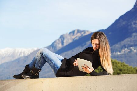 Young Caucasian woman with tablet lying on the wall photo