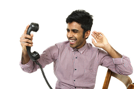 young man struggling with a crazy telephone , portrait on white background photo