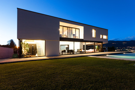 houses on water: Modern villa with pool, view from garden, night scene Stock Photo