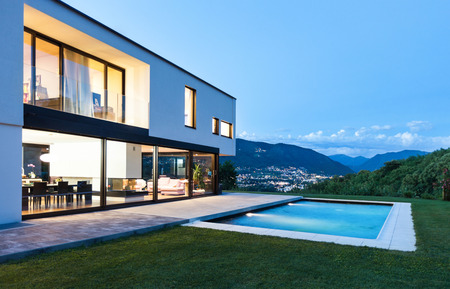 outside of house: Modern villa with pool, night scene