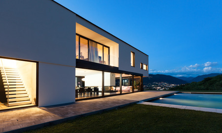 luxury home exterior: Modern villa with pool, night scene