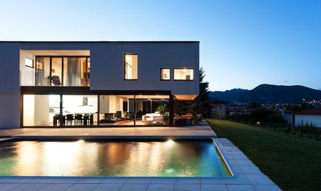 modern garden: Modern villa, night scene,view from poolside