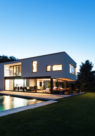 case moderne: Villa moderna con piscina, vista dal giardino, scena notturna Archivio Fotografico