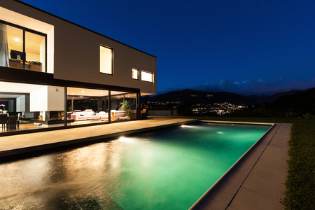 contemporary house: Modern villa, night scene,view from poolside