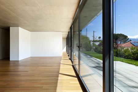 housing styles: modern concrete house with hardwood floor, large windows