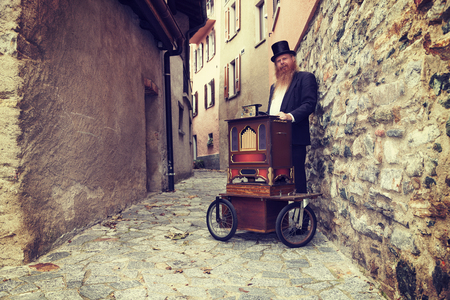 odd: fulvous man with organ outdoors