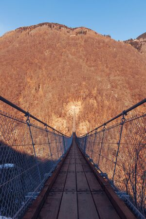 Mountain landscape with suspension bridge over the valley photo