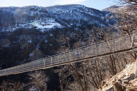 drawbridge: Mountain landscape with suspension bridge over the valley Stock Photo