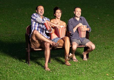 três amigos assistindo a um filme no cinema ao ar livre