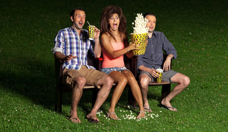 horror movies: three friends watching a movie at cinema outdoors