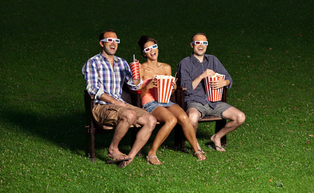 entertainment funny: three friends watching a movie at cinema outdoors