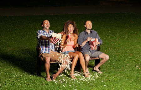 horror movie: three friends watching a movie at cinema outdoors