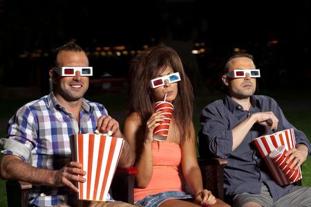 ni�as sonriendo: tres amigos viendo una pel�cula en el cine al aire libre
