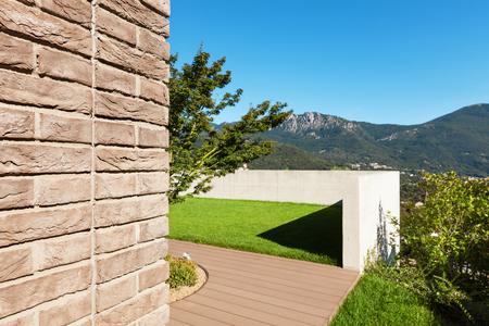 modern garden: Modern house in cement and bricks, garden view