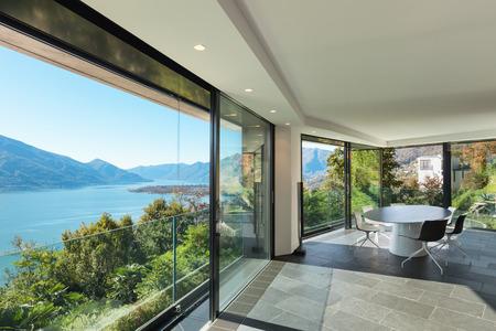 Interior de la casa moderna, amplia sala comedor con paredes de cristal