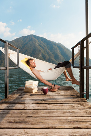 rest day: portrait of young man on the dock of Lake