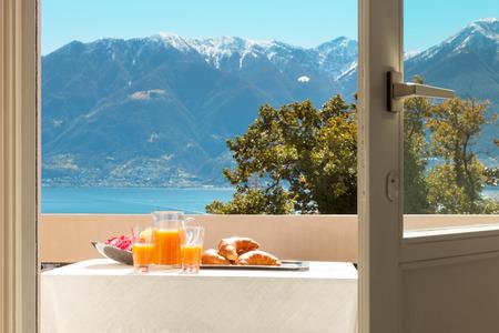petit dejeuner: petit déjeuner traditionnel sur le balcon d'une maison, vue sur le lac