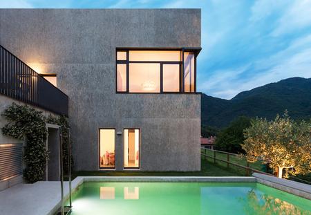 Externe van een modern huis met zwembad nachtscène royalty vrije