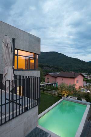 outside house: external of a modern house with pool, evening scene