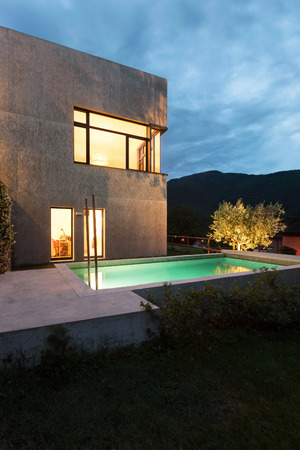 illuminations: external of a modern house with pool, night scene