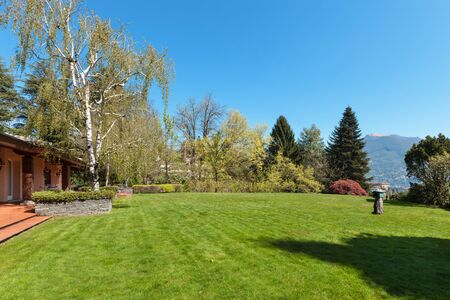 home and garden: Green lawn and beautiful house in a sunny spring day