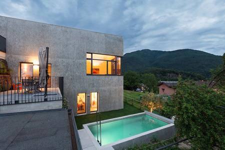 case moderne: esterno di una casa moderna con piscina, sera scena