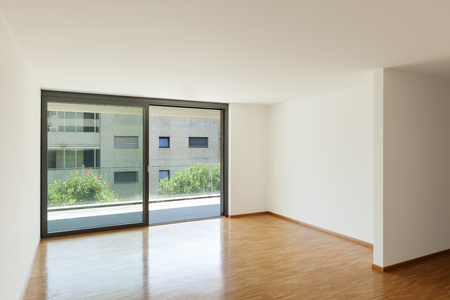 apartment living: interior of an apartment, empty living room with balcony, parquet floor