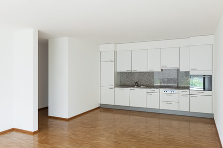 apartment living: interior of an apartment, empty living room with kitchen, parquet floor Stock Photo