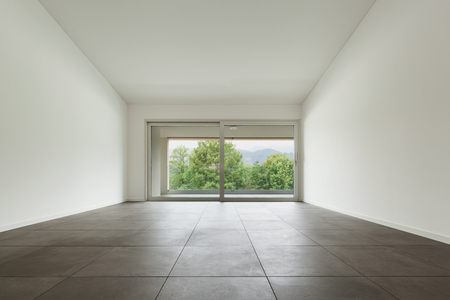 interior of new apartment, wide room with window, tiled  floor