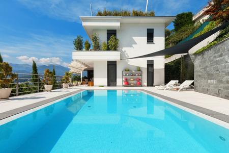 fachada: hermosa casa blanca con piscina, día de verano