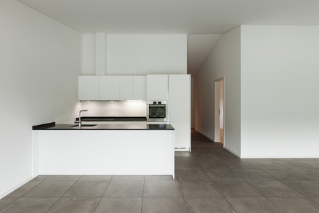 cement wall: interior of new apartment, empty room with domestic kitchen
