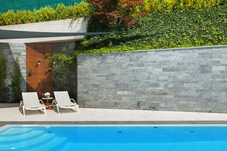 piso piedra: hermosa casa, hamacas vista desde la piscina, día de verano Foto de archivo