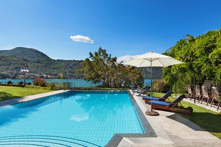 hotel resort: external of a villa, beautiful swimming pool overlooking the lake