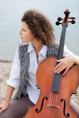 shore: closeup of a young woman with her cello, outdoor