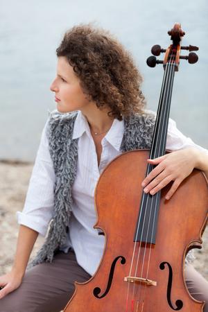 mujeres sentadas: primer plano de una mujer joven con su violonchelo, al aire libre Foto de archivo