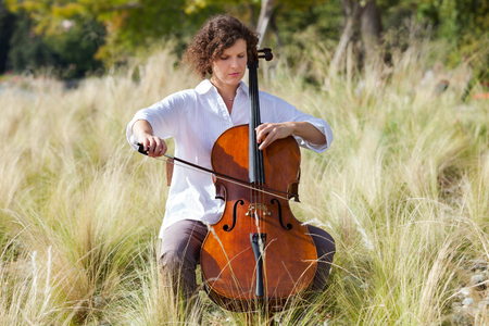 cellos: woman playing the cello between fields