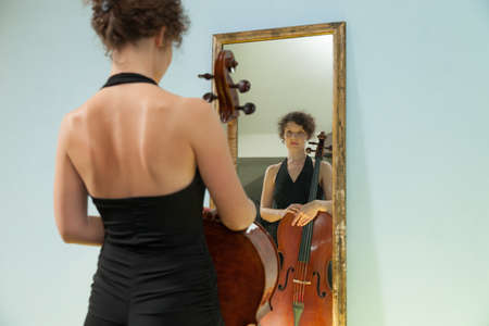 attractive  female: beautiful woman with cello looking into a mirror at herself