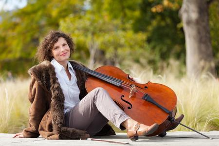 cellist: Portrait of young cellist, outdoors Stock Photo
