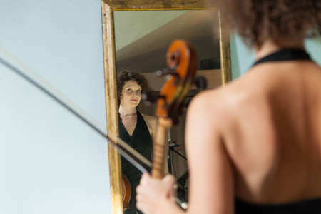 young musician: beautiful woman with cello looking into a mirror at herself
